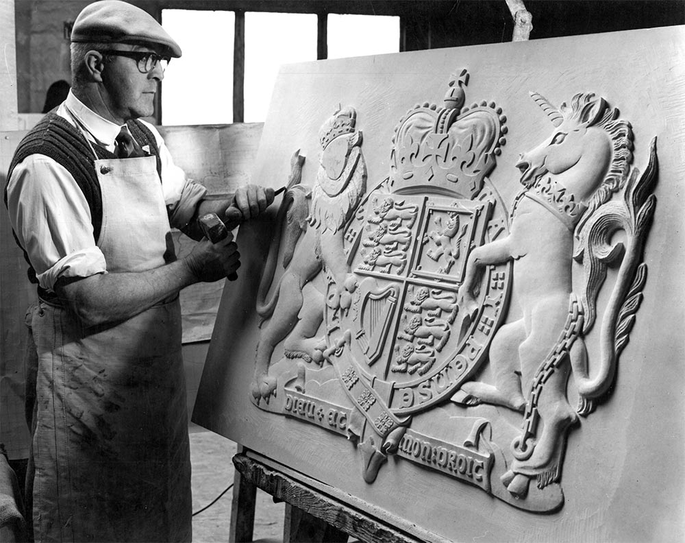 Lead carver Harry Garland finishing Portland stone coat of arms.